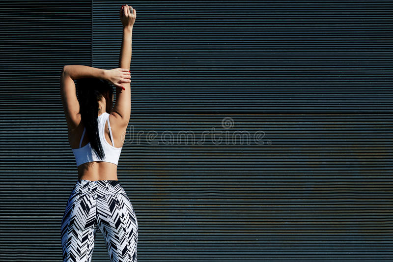 Mujer atlética de la visión trasera con la figura perfecta y las nalgas que hacen posiciones en cuclillas contra la pared con el  fotos de archivo libres de regalías