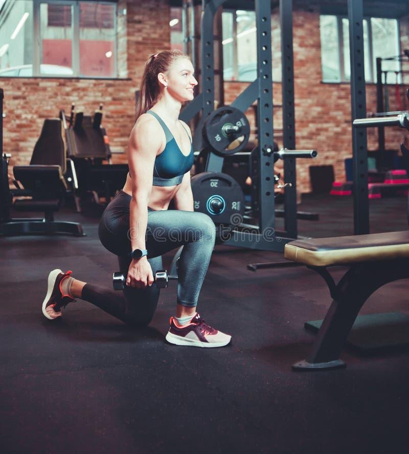 Mujer atlética de Smilling que hace estocadas con pesas de gimnasia fotografía de archivo libre de regalías