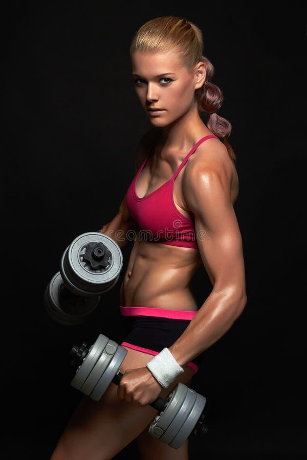 Mujer atlética del culturista con pesas de gimnasia muchacha rubia hermosa con los músculos imagen de archivo