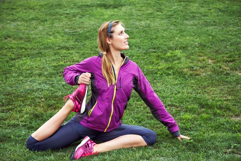 Mujer atlética deportiva que hace aptitud en una hierba aire libre de la yoga de los deportes foto de archivo