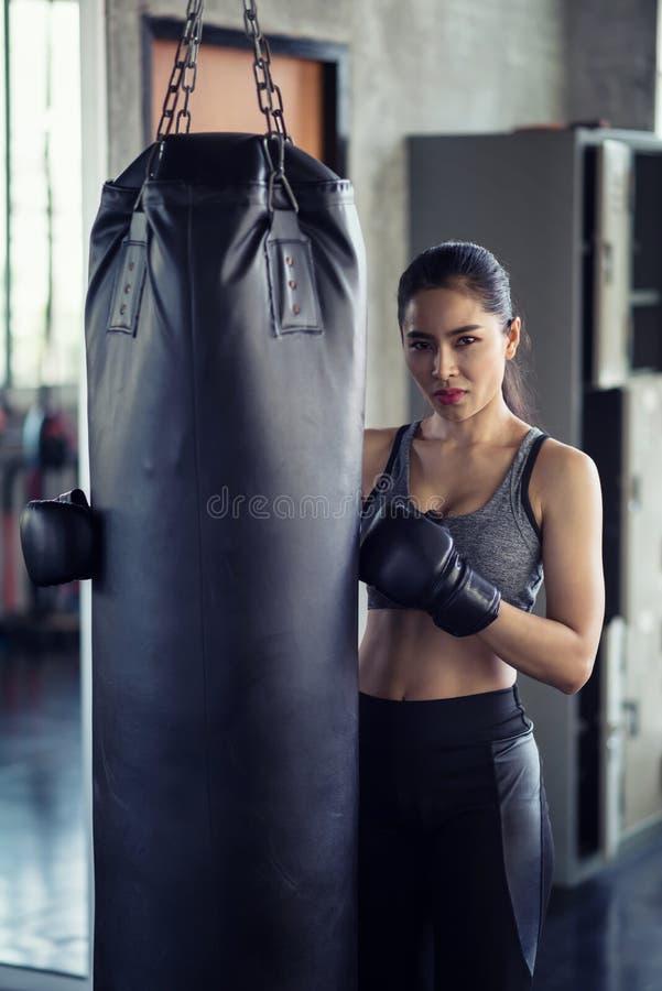 Mujer atlética en el saco de arena en gimnasio fotos de archivo