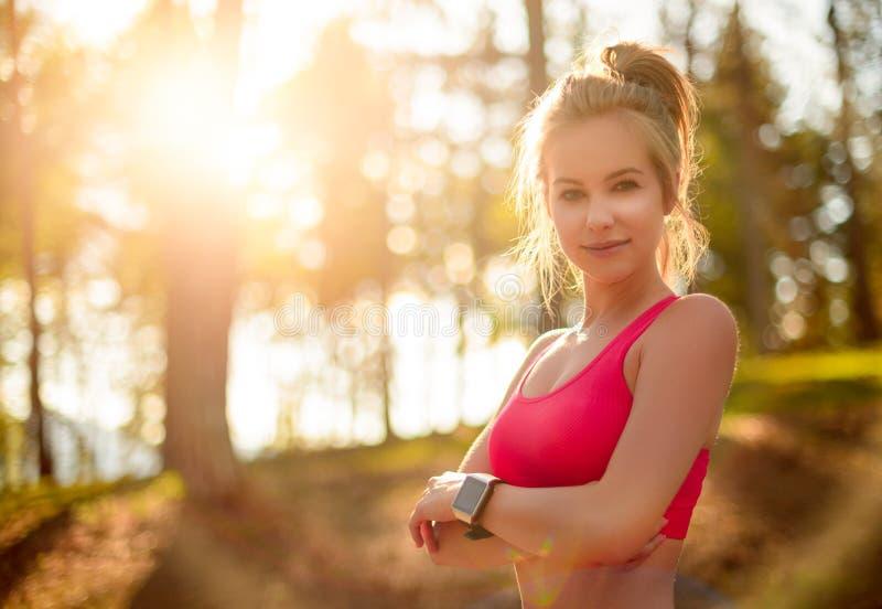 Mujer atlética en un bosque, reloj elegante que lleva del ajuste atractivo, tomando una rotura del entrenamiento intenso Deporte, imágenes de archivo libres de regalías