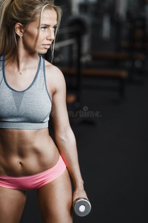 Mujer atlética hermosa atractiva que bombea para arriba muscules con pesas de gimnasia imagen de archivo libre de regalías