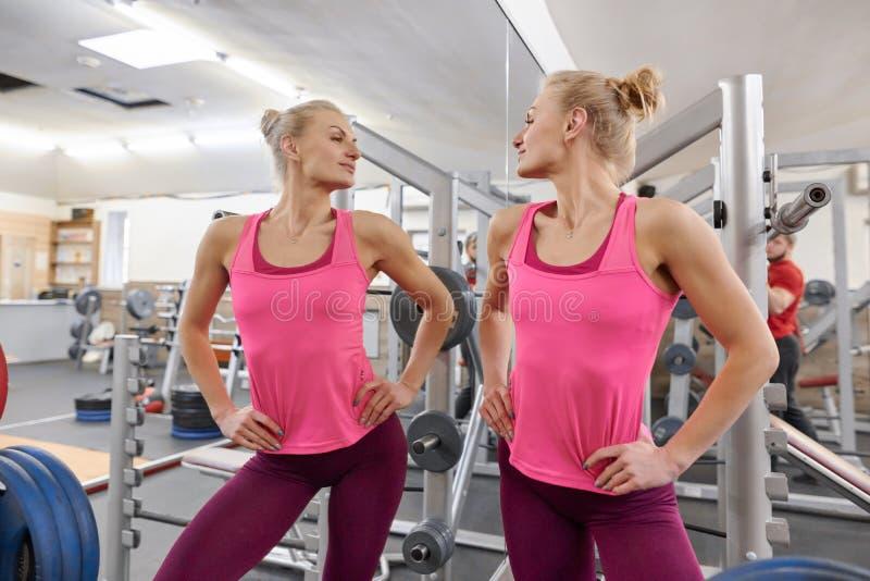 Mujer atlética hermosa joven rubia en el gimnasio que mira en el espejo Concepto sano de la forma de vida del deporte de la aptit fotos de archivo