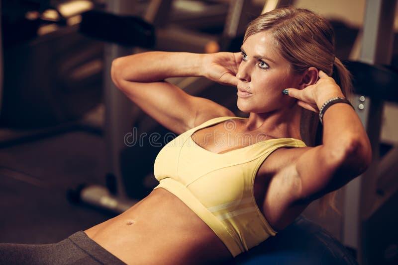 Mujer atlética hermosa que trabaja intervalos del ab en aptitud foto de archivo libre de regalías