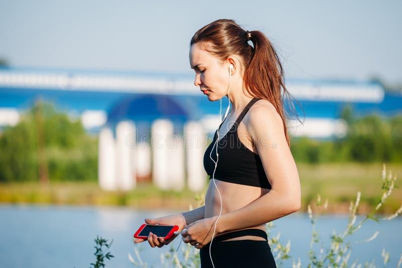 Mujer atlética joven en el corredor de la playa que escucha la música con los auriculares fotos de archivo