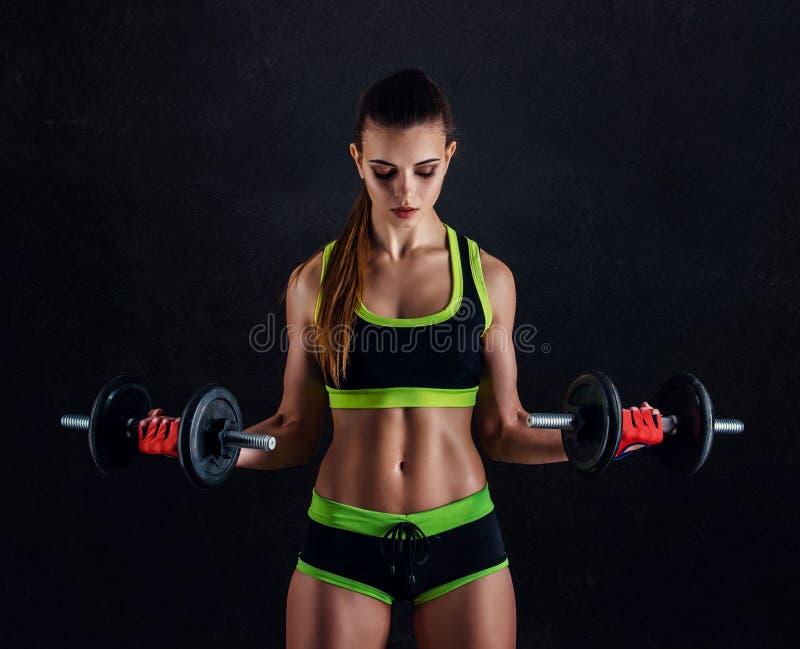 Mujer atlética joven en ropa de deportes con pesas de gimnasia en estudio contra fondo negro Figura femenina ideal de los deporte fotos de archivo