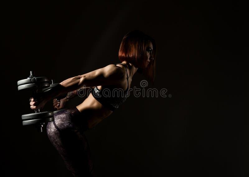 Mujer atlética joven en ropa de deportes con un dumbbellson un fondo oscuro Espacio libre para el texto imagen de archivo libre de regalías