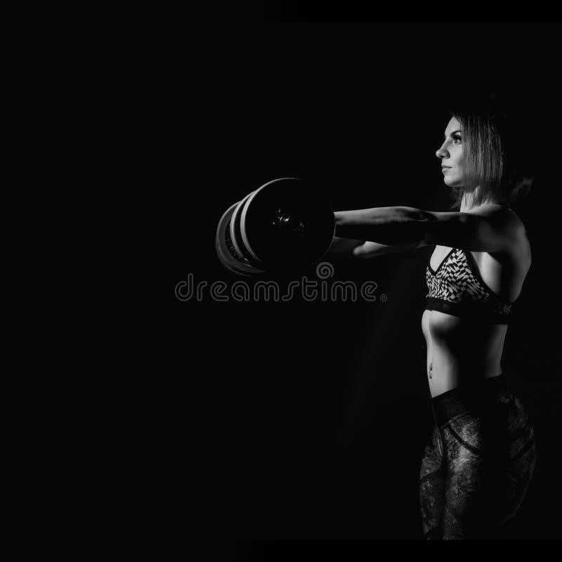 Mujer atlética joven en ropa de deportes con un dumbbellson un fondo oscuro Espacio libre para su texto fotografía de archivo libre de regalías