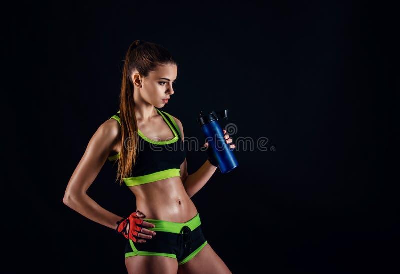 Mujer atlética joven en ropa de deportes con una coctelera en estudio contra fondo negro Figura femenina ideal de los deportes Mu fotos de archivo libres de regalías