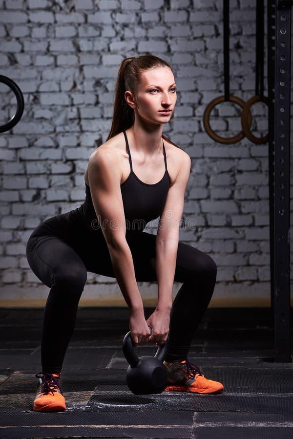 Mujer atlética joven que ejercita con el kettlebell mientras que estando en la posición agazapada contra la pared de ladrillo fotografía de archivo