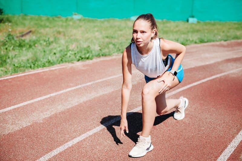 Mujer atlética joven que se prepara para correr en el estadio, al aire libre Concepto de forma de vida sana fotografía de archivo
