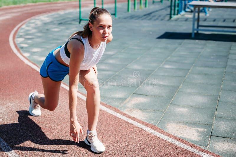 Mujer atlética joven que se prepara para correr en el estadio, al aire libre El concepto de forma de vida sana imagen de archivo