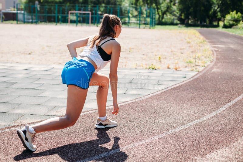 Mujer atlética joven que se prepara para correr en el estadio, al aire libre Visión desde la parte posterior El concepto de forma imagen de archivo