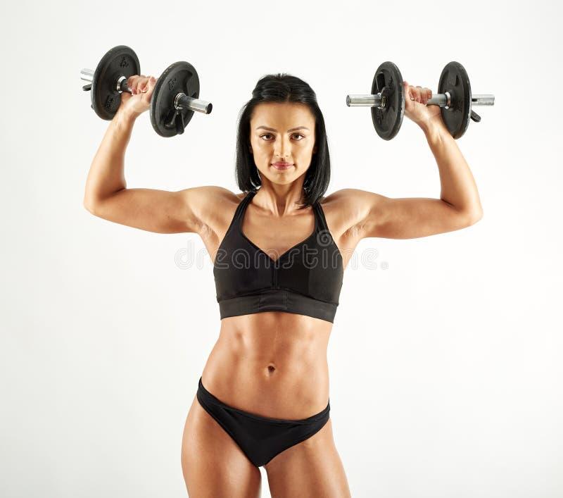 Mujer atlética joven que se resuelve con pesas de gimnasia imagenes de archivo