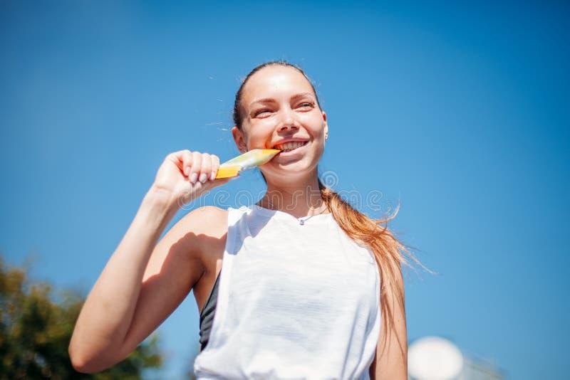 Mujer atlética joven que sostiene la barra de la proteína en sus dientes imagenes de archivo