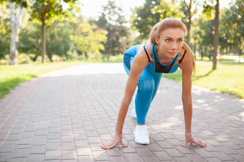Mujer atlética magnífica que se resuelve en el parque por la mañana imágenes de archivo libres de regalías