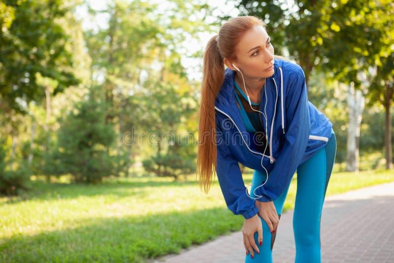 Mujer atlética magnífica que se resuelve en el parque por la mañana imagen de archivo