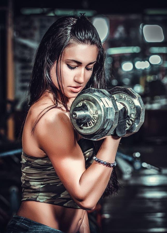 Mujer atlética que bombea para arriba muscules con pesas de gimnasia fotografía de archivo