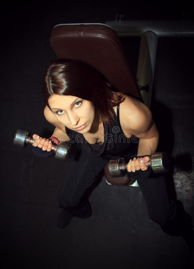 Mujer atlética que bombea para arriba muscules con pesas de gimnasia en foto de archivo libre de regalías
