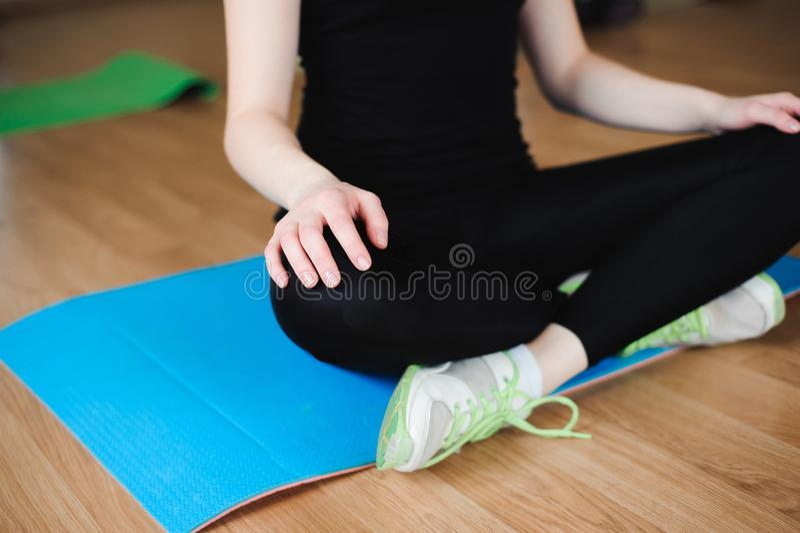 Mujer atlética que hace ejercicios de la relajación en clase del gimnasio fotografía de archivo