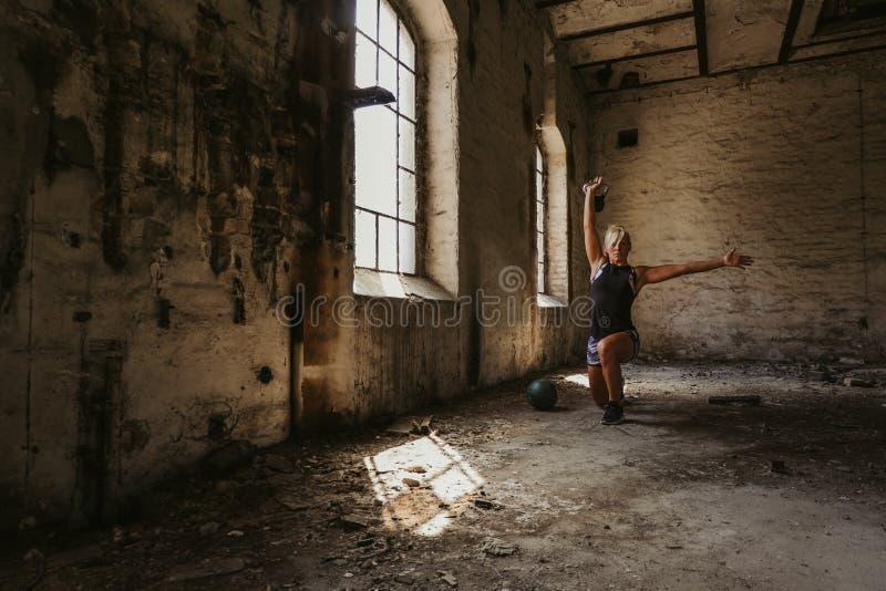 Mujer atlética que hace el kettlebell para lanzarse para clavar un edificio viejo fotografía de archivo