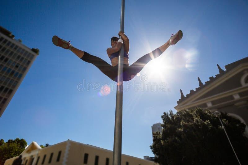 Mujer atlética que hace la gimnasia en placa de calle fotos de archivo