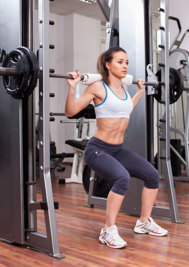 Mujer atlética que hace posiciones en cuclillas en el gimnasio fotos de archivo libres de regalías