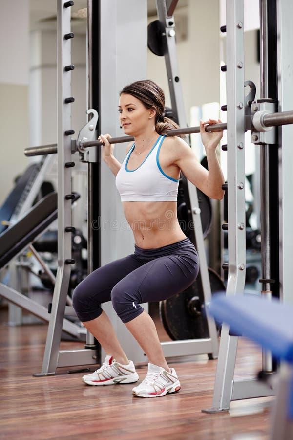 Mujer atlética que hace posiciones en cuclillas en el gimnasio imagen de archivo