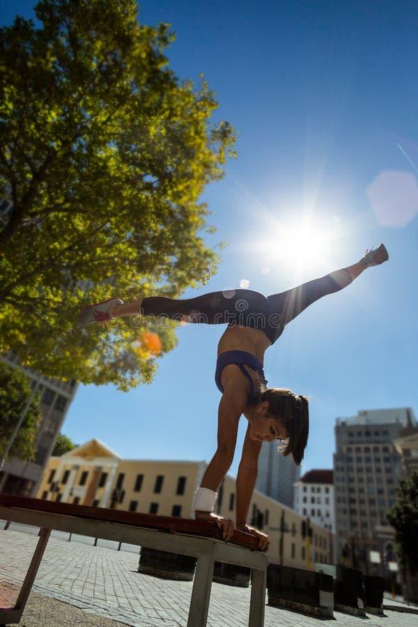 Mujer atlética que realiza posición del pino y que hace fractura en banco foto de archivo