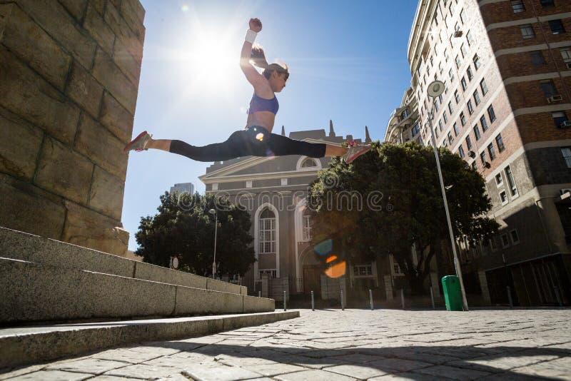 Mujer atlética que salta de las escaleras y que hace fractura en el aire fotos de archivo
