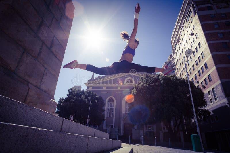 Mujer atlética que salta de las escaleras y que hace fractura en el aire imagen de archivo libre de regalías