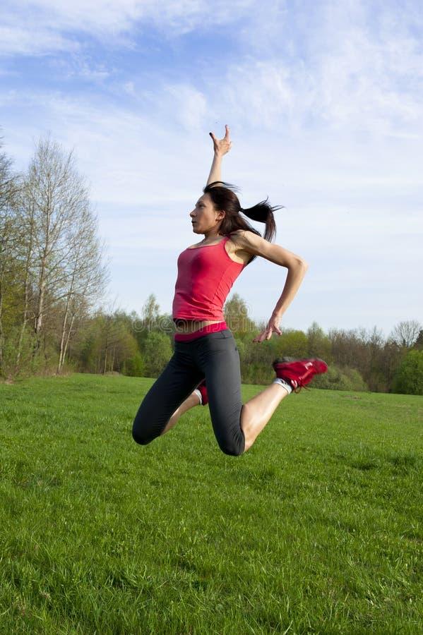 Mujer atlética que salta en el parque