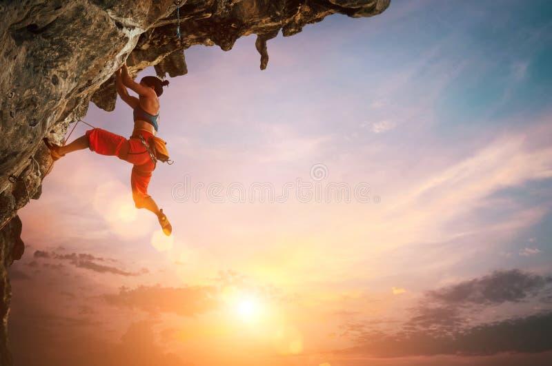 Mujer atlética que sube en roca sobresaliente del acantilado con el fondo colorido del cielo de la puesta del sol foto de archivo