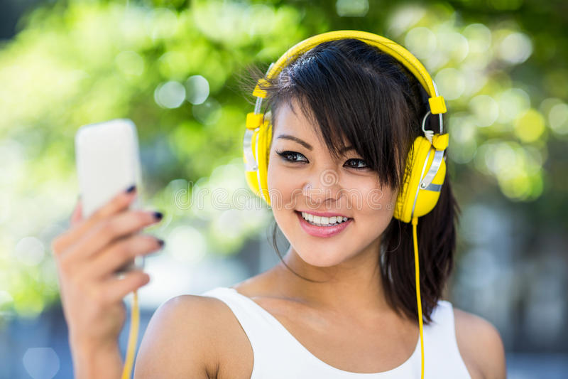 Mujer atlética sonriente que lleva los auriculares amarillos y tomar selfies imagen de archivo