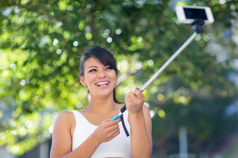 Mujer atlética sonriente que toma selfies con el selfiestick imágenes de archivo libres de regalías