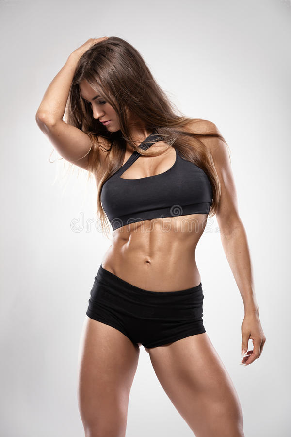 Mujer atractiva agradable de la aptitud que muestra los músculos abdominales imagen de archivo libre de regalías