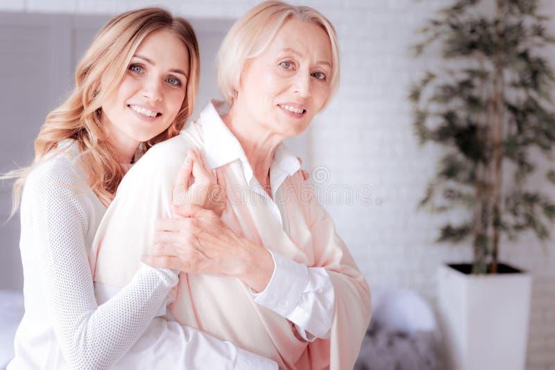 Mujer atractiva agradable que abraza a su madre fotos de archivo libres de regalías