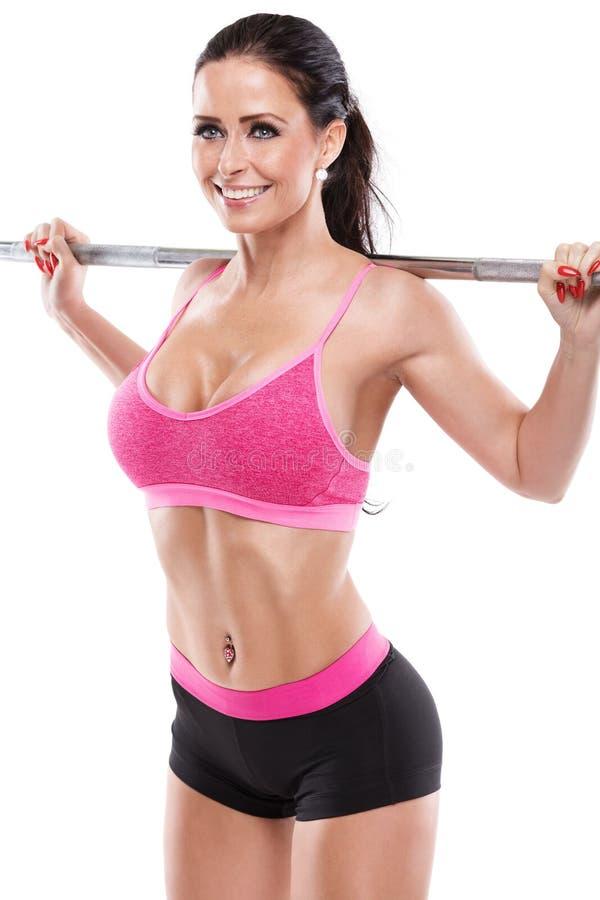 Mujer atractiva agradable que hace entrenamiento agazapado con la pesa de gimnasia grande, retocada foto de archivo libre de regalías