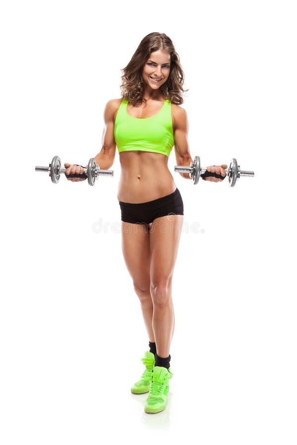 Mujer atractiva agradable que hace entrenamiento con la pesa de gimnasia (retocada) foto de archivo libre de regalías