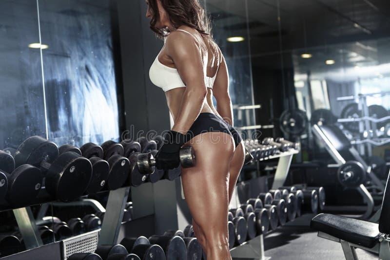 Mujer atractiva agradable que hace entrenamiento con pesas de gimnasia imagenes de archivo
