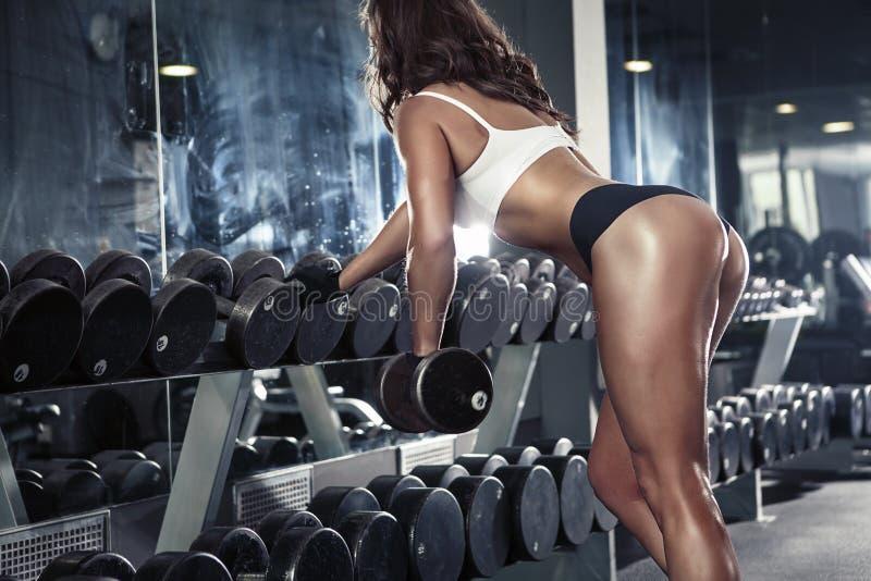 Mujer atractiva agradable que hace entrenamiento con pesas de gimnasia imágenes de archivo libres de regalías