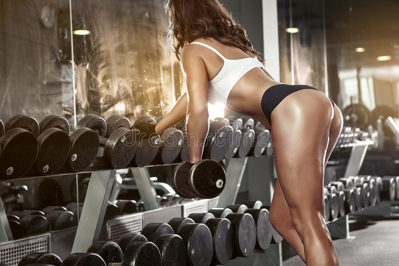 Mujer atractiva agradable que hace entrenamiento con pesas de gimnasia fotografía de archivo