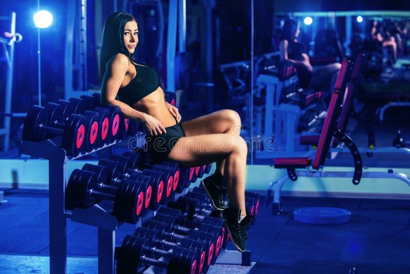 Mujer atractiva agradable que hace entrenamiento con pesas de gimnasia en gimnasio fotografía de archivo libre de regalías