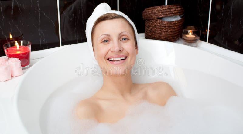 Mujer atractiva alegre en un baño de burbuja imagen de archivo libre de regalías