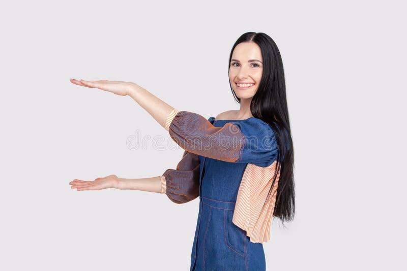 Mujer atractiva alegre joven en el vestido azul claro de los vaqueros que muestra algo grande con las manos Estudiante moreno que foto de archivo
