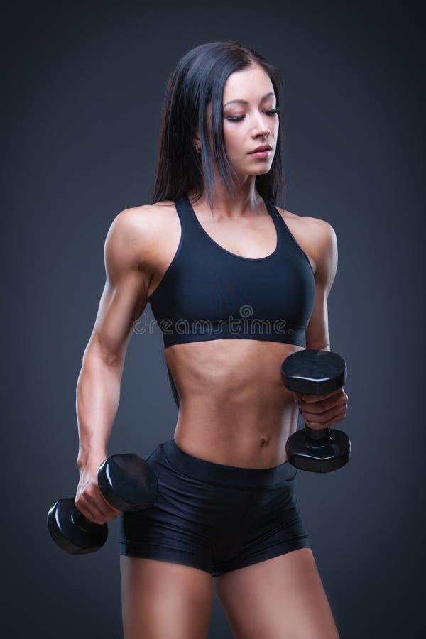 Mujer atractiva atlética brutal que bombea para arriba muscules con pesas de gimnasia El concepto de ejercicio se divierte, hacie imagenes de archivo