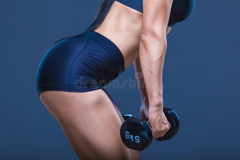 Mujer atractiva atlética brutal que bombea para arriba muscules con pesas de gimnasia El concepto de ejercicio se divierte, hacie fotografía de archivo libre de regalías