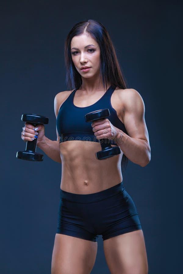 Mujer atractiva atlética brutal que bombea para arriba muscules con pesas de gimnasia El concepto de ejercicio se divierte, hacie imagen de archivo libre de regalías