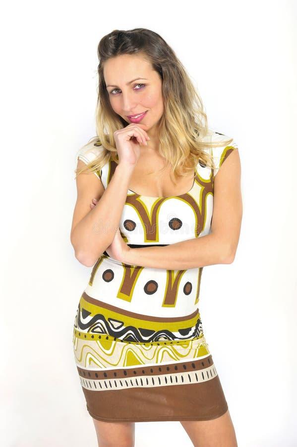 Mujer atractiva atractiva con el pelo rubio en el vestido de moda corto que parece interesante y atractivo foto de archivo libre de regalías